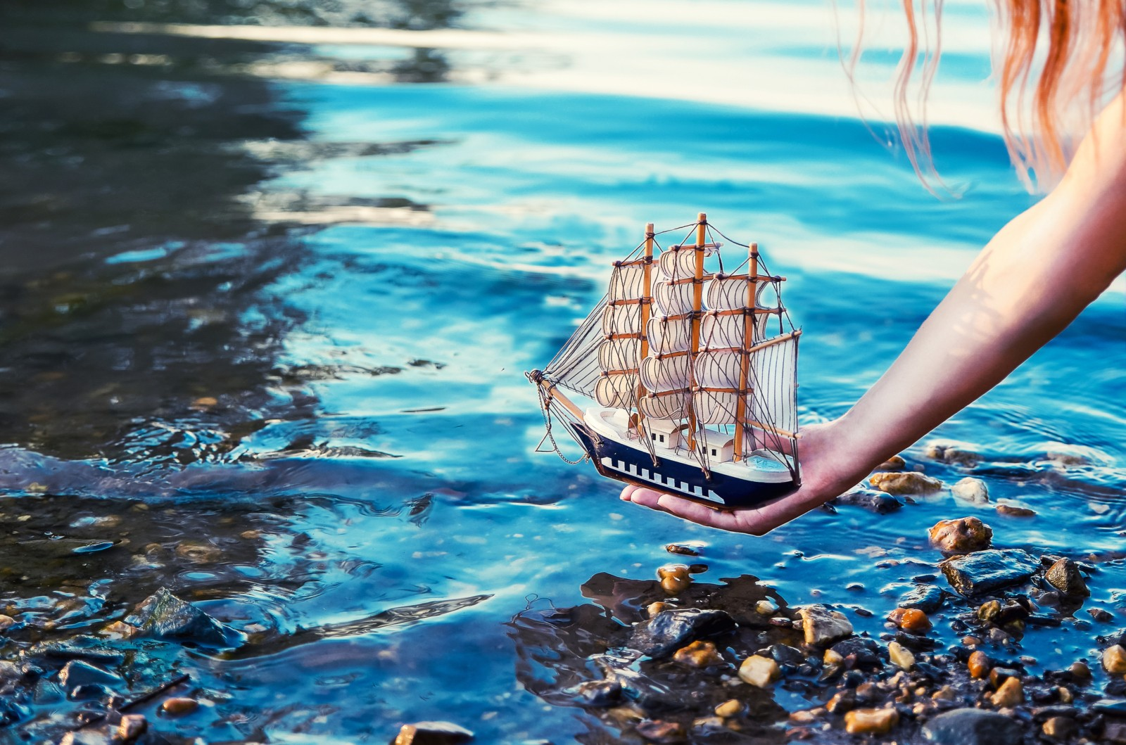 Girl holding sailboat in water